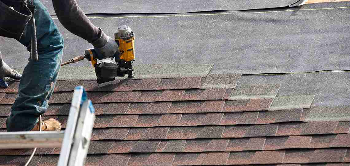 Roofer attaching shingles